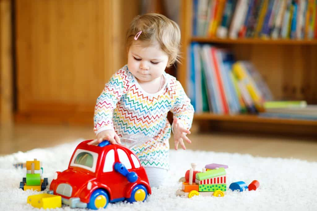 Adorable cute beautiful little baby girl playing with educational wooden toys at home or nursery. Toddler with colorful red car