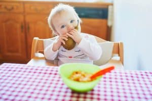 Cute baby girl eating pear in the kitchen