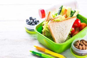Lunch box with sandwich, vegetables, banana, water, nuts and ber